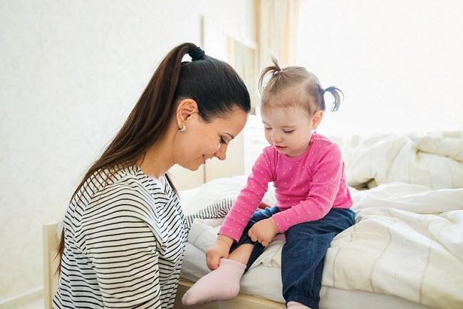 ребенок учится одевать носочки