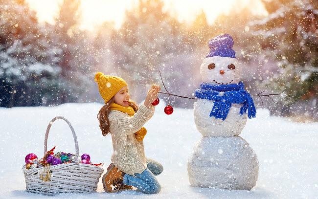 девочка наряжает снеговика