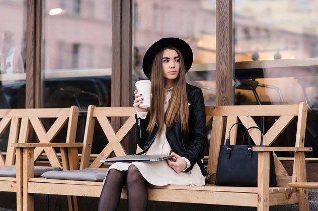 девушка одна сидит на скамейке