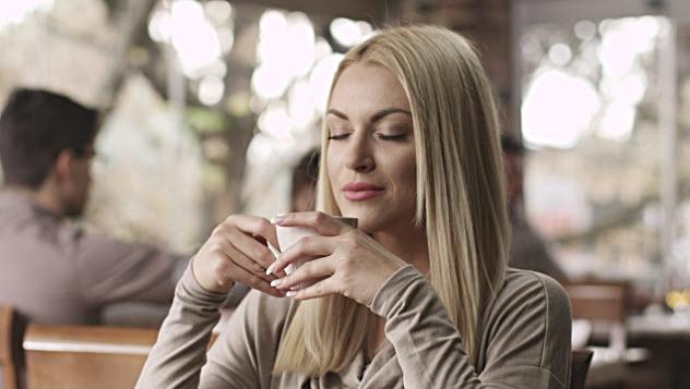 девушка пьет кофе в кафе
