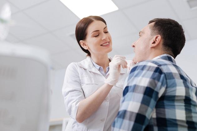 девушка врач осматривает горло мужчины