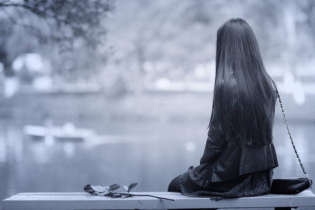 красивая одинокая девушка сидит на скамейке