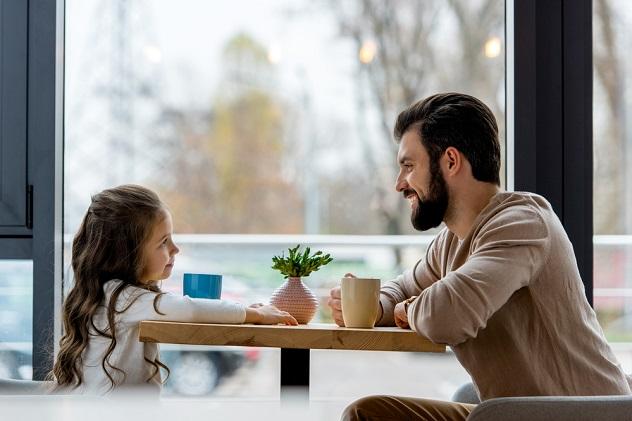 отец и дочь мило беседуют в кафе