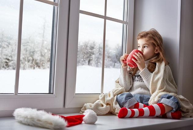 девочка пьет кофе и смотрит в окно