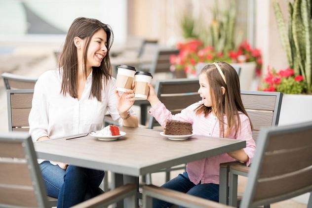 мама и дочка, делают ура с кофе в кафе