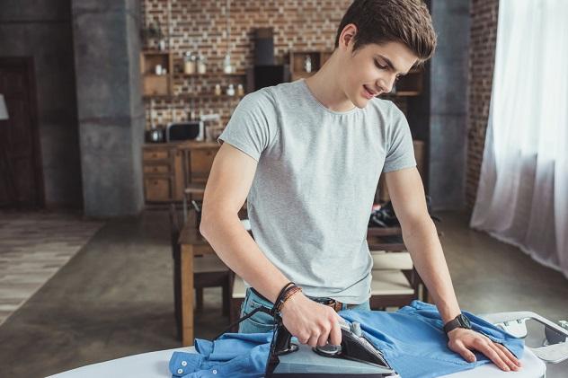 парень гладит рубашку