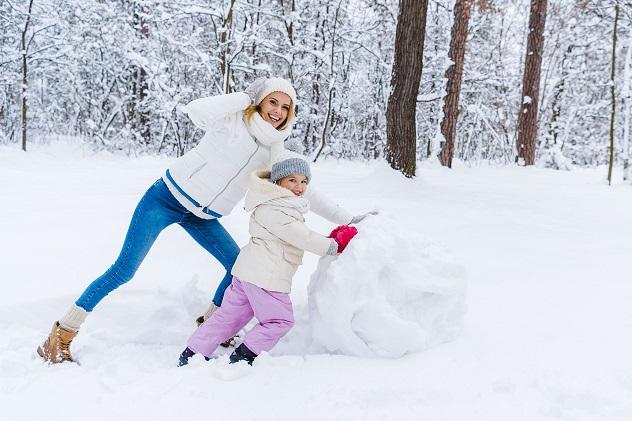 мама с дочкой лепят снеговика
