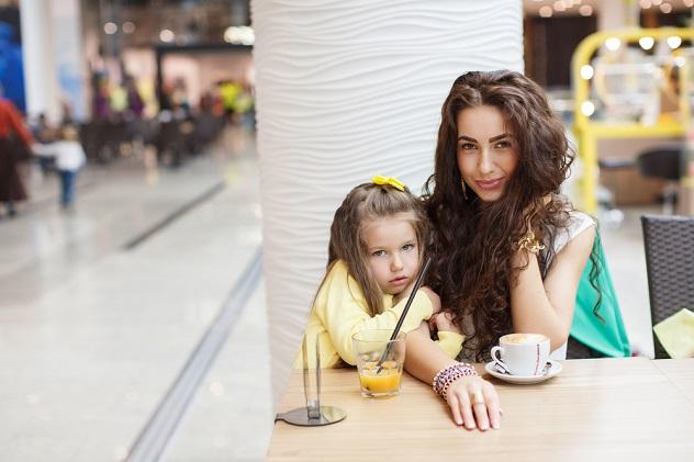 мама с дочкой пью кофе и сок
