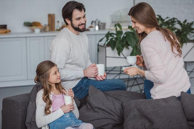 родители и дочка пьют кофе и молоко